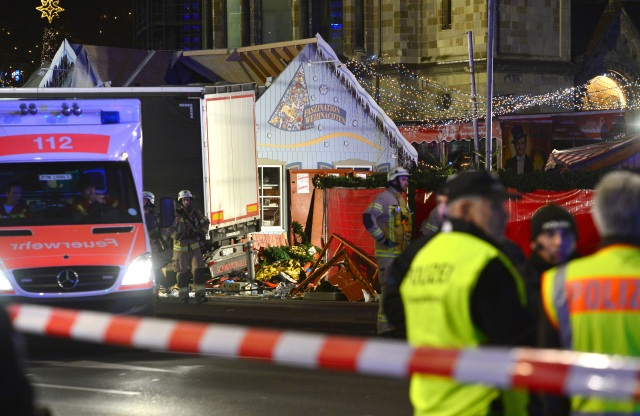 Rescue workers inspect the scene where a truck crashed into a Christmas market in Berlin Dec. 19. (CNS/Reuters)