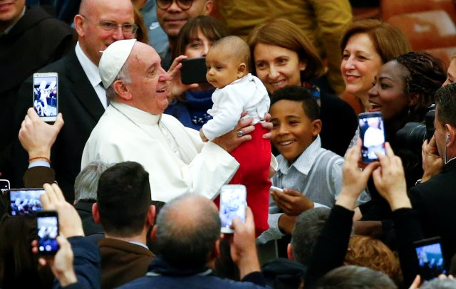 Pope Francis holds a child as he arrives to lead a special audience with Vatican workers Dec. 22 in Paul VI hall. (CNS/Reuters)