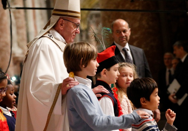 Pope Francis walks with children at the conclusion of Christmas Eve Mass in Peter's Basilica at the Vatican Dec. 24. (CNS/Paul Haring)