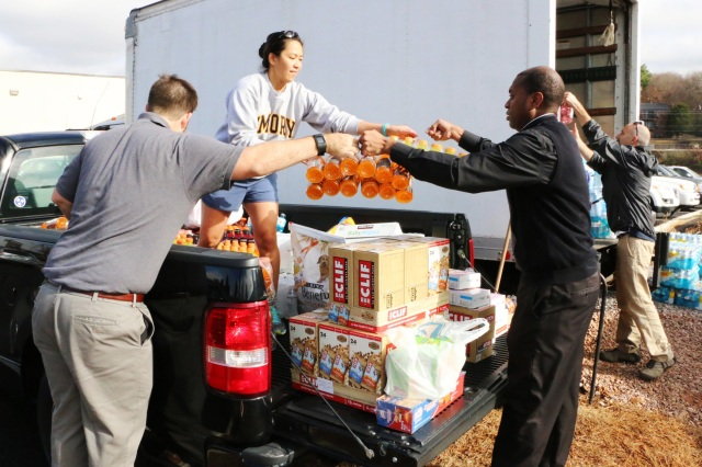 Father Arthur Torres, associate pastor at Sacred Heart Cathedral in Knoxville, Tenn., assists volunteers Nov. 29 in unloading items donated for victims of the wildfires that ravaged the Great Smoky Mountains region. (CNS photo/Bill Brewer, The East Tennessee Catholic)