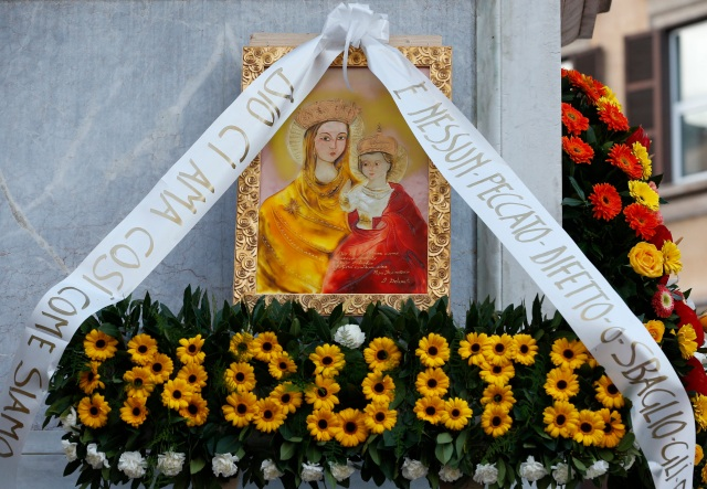 Flowers decorate an image of Mary and the child Jesus at the base of a Marian statue at the Spanish Steps in Rome Dec. 8, the feast of the Immaculate Conception. Rome's firefighters have placed flowers high atop the statue every year since 1857. (CNS photo/Paul Haring)
