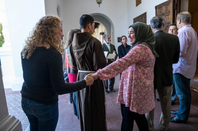 Kate Arenchild, a Lasallian peer minister for fair trade at St. Mary's College in Moraga, Calif., and Roshun Rahimi, a student involved in the college's Mission and Ministry Center, greet each other at the dedication of the college's Interfaith Sacred Space. (CNS photo/Gerry Serrano, courtesy St. Mary's College)