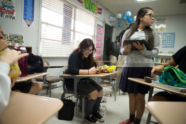 Alejandra Rodriguez checks her smartphone during lunch at St. Joseph Academy in Brownsville, Texas. Of the 563 students enrolled at the Marist-run school, 54 commute from Mexico. (CNS/Tyler Orsburn)