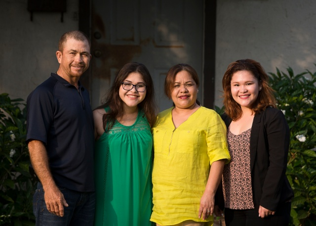 Alejandra Rodriguez, in green, poses for a photo with her parents, Gustavo and Columba, and older sister Sofia, right, outside their home in Brownsville, Texas. (CNS/Tyler Orsburn)