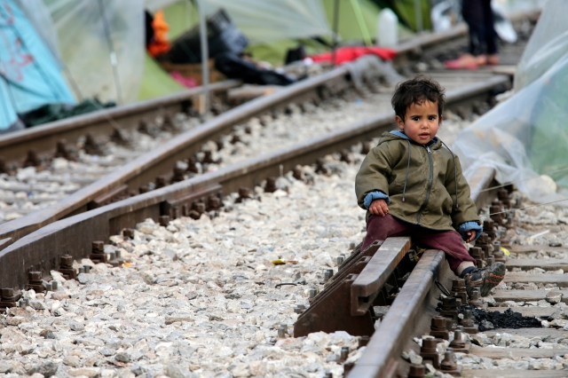 A child sits on railroad tracks near a makeshift camp for migrants in 2016 at the Greek-Macedonian border near the village of in Idomeni, Greece. (CNS/EPA)