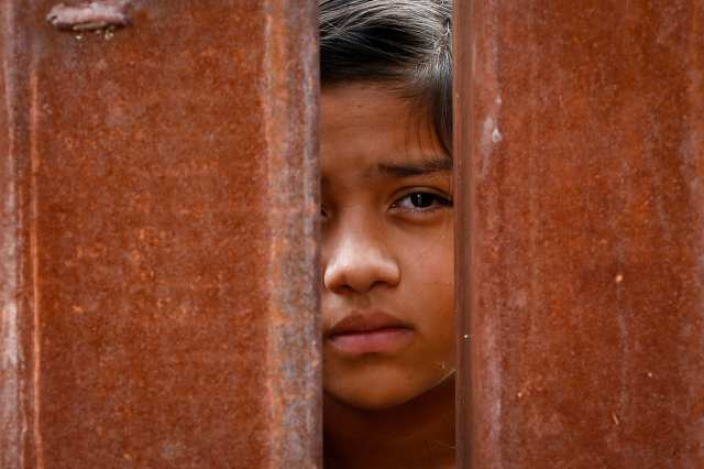 A Mexican girl peers through the fence during Mass at the international border in Nogales, Ariz., last October. The liturgy was celebrated on both sides of the U.S.-Mexico border. (CNS/Nancy Wiechec)