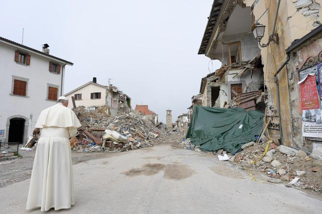 Pope Francis prays as he visits the earthquake-ravaged town of Amatrice, Italy, in August 2016. (CNS/L'Osservatore Romano)
