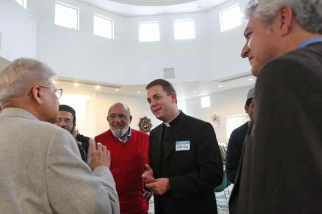 Father Gregory Rannazzisi chats with Muslim men during an open house in 2010 at the Islamic Center of Long Island in Westbury, N.Y. Father Rannazissi, a member of the ecumenical and interfaith commission of the Diocese of Rockville Centre, N.Y., is the diocese's liaison with Long Island's Muslim population. (CNS/Gregory A. Shemitz)