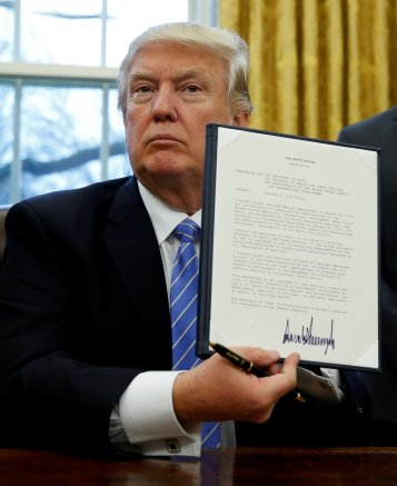 "President Donald J. Trump holds up his executive order reinstating the ""Mexico City Policy"" banning federal funding of abortion-providing groups abroad after he signed it Jan. 23 in the Oval Office of the White House in Washington. (CNS/Reuters)"