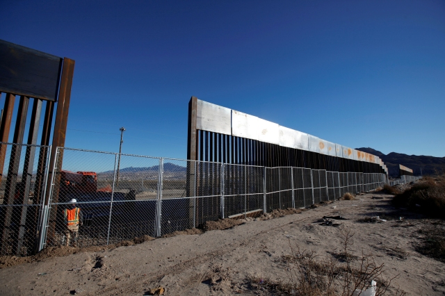 A worker stands next to a newly built section of the U.S.-Mexico border wall in 2016 at Sunland Park, New Mexico, opposite the Mexican border city of Ciudad Juarez, Mexico. (CNS photo/Jose Luis Gonzalez, Reuters)