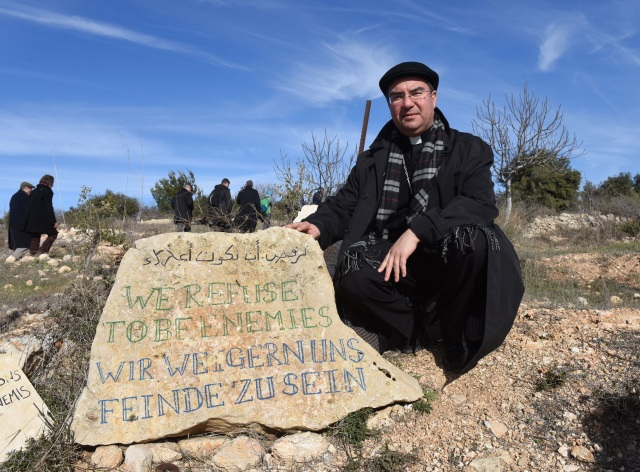 "Bishop Oscar Cantu of Las Cruces, N.M., kneels by a stone that reads ""We Refuse To Be Enemies"" Jan. 16 at the entrance to the Tent of Nations in the West Bank, near Bethlehem. (CNS photo/Debbie Hill)"
