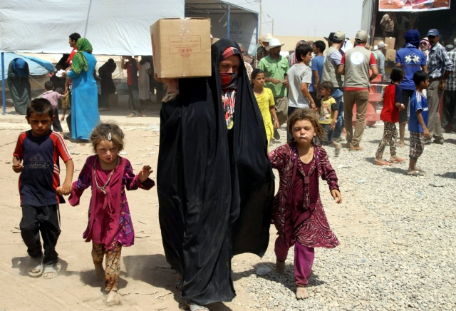 An Iraqi woman carries humanitarian aid alongside her children Dec. 23 at a camp for displaced people near Irbil, Iraq. (CNS photo/Kamal Akrayi, EPA)