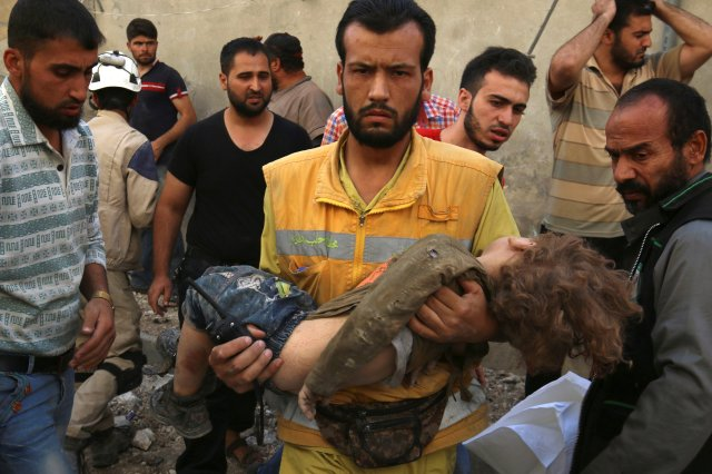 A medic carries a dead child Oct. 4 after airstrikes in a rebel-held area of Aleppo, Syria. (CNS/Reuters)