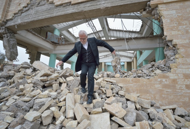 Father Emanuel Youkhana, an archimandrite of the Assyrian Church of the East, walks through the rubble of a demolished church in Mosul, Iraq, Jan. 27. (CNS/Paul Jeffrey)