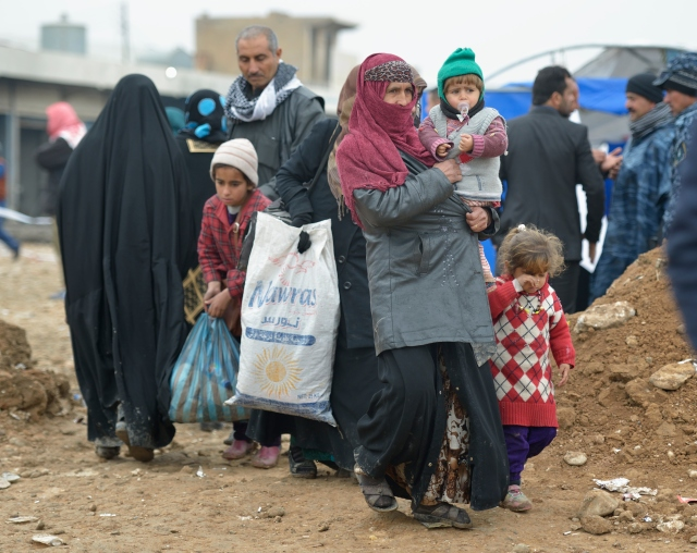 Displaced by fighting between the Iraqi army and the Islamic State group, a family leaves a processing center for displaced families Jan. 27 outside Mosul, Iraq. A survey found Americans feeling more positive about Muslims than they did in 2014. (CNS/Paul Jeffrey)