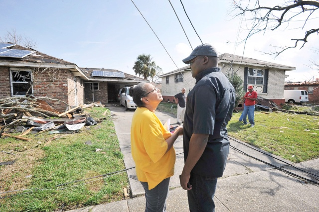 Father Geoffrey Omondi Muga, right, a member of the Franciscan Missionaries of Hope who is pastor of Resurrection of Our Lord Parish in New Orleans East, consoles parishioner Carol Adams. Her brick home was heavily damaged by a tornado Feb. 7. (CNS/Peter Finney Jr., Clarion Herald)