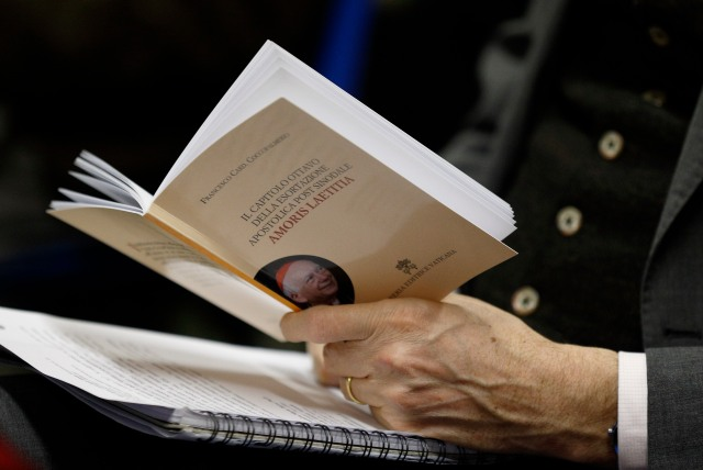 """A journalist holds a copy of a book by Cardinal Francesco Coccopalmerio, president of the Pontifical Council for Legislative Texts, on Pope Francis' apostolic exhortation, """"Amoris Laetitia,"""" during its presentation at the Vatican Feb. 14.(CNS/Paul Haring)"""