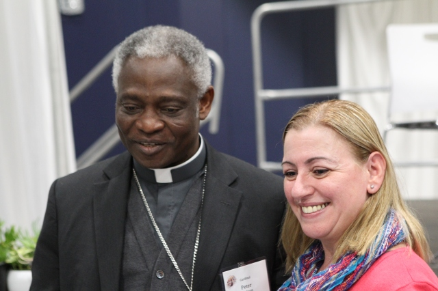 Cardinal Peter Turkson, prefect of the Vatican's Dicastery for Promoting Integral Human Development, poses for a photo Feb. 16 with Lira DeMoraes, a volunteer with the Merrimack Valley Project in Massachussetts at the start of the U.S. regional World Meeting of Popular Movements in Modesto, Calif. (CNS/Dennis Sadowski)