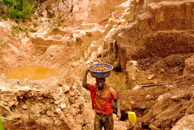"A Congolese mine worker carries gold-rich earth out of a pit for water processing in 2009 in Chudja. Church leaders say telling companies they no longer have to disclose whether their firms use ""conflict minerals"" would be a bad move. (CNS/EPA)"