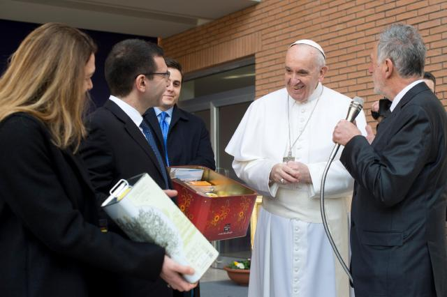Pope Francis smiles as he receives gifts during a Feb. 17 meeting at Roma Tre University. Students presented him with olive oil produced from the university's trees and products from a farm they help run on land confiscated by the government in an anti-Mafia operation. (CNS/L'Osservatore Romano)