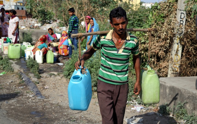 A man carries containers filled with drinking water after taking it from a public tap at a roadside in Jammu, India, in 2016. (CNS/EPA)