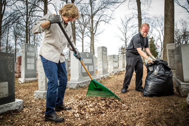 Nancy Wagoner and Father William Dotson of St. Patrick Parish in Wentzville, Mo., clean up leaves Feb. 22 at Chesed Shel Emeth Cemetery in University City, Mo., after a vandalism attack. The incident at the cemetery near St. Louis was repeated in suburban Philadelphia Feb. 26. (CNS/Lisa Johnston, St. Louis Review)