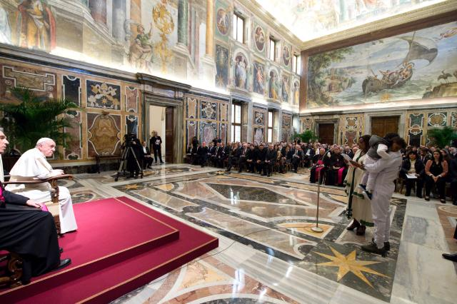 A refugee couple from Eritrea tell Pope Francis about their journey to safety during a meeting Feb. 21 at the Vatican with participants in the International Forum on Migration and Peace. (CNS/L'Osservatore Romano)