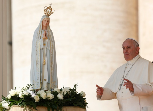 Pope Francis gestures toward the crowd as he points out a statue of Our Lady of Fatima during his general audience on her feast day in 2015. (CNS/Paul Haring)