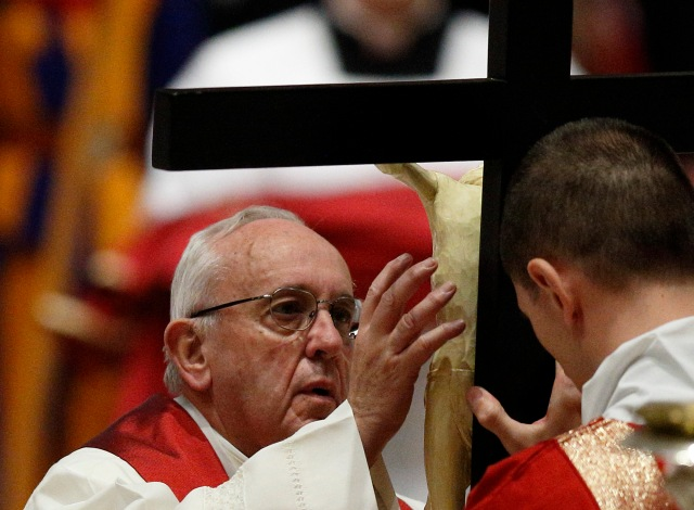Pope Francis reverences a crucifix during the Good Friday service in St. Peter's Basilica at the Vatican last year. (CNS photo/Paul Haring)
