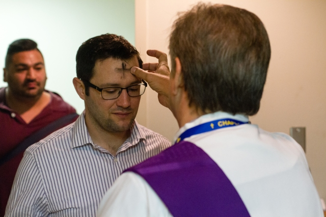 Deacon Ray Oden of St. James Catholic Church in Spring, Texas, marks a cross with ashes on a man's forehead in the Interfaith Chapel at Bush Intercontinental Airport in Houston on Ash Wednesday, March 1. (CNS/James Ramos, Texas Catholic Herald)