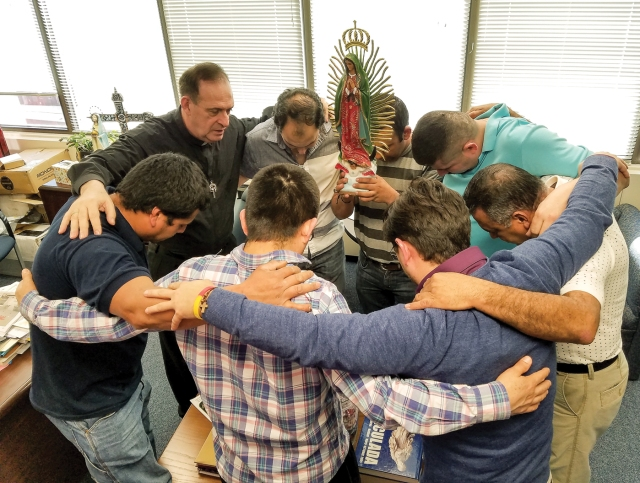 Father Jose E. Hoyos, director of the Spanish Apostolate Office of the Diocese of Arlington, Va., prays with a group of Hispanic leaders in his office. (CNS/Mary Stachyra Lopez, Arlington Catholic Herald)