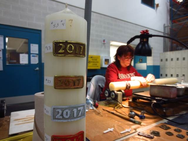Production employee Rose Marie Dixon adds decorations to a paschal candle at the A.I. Root Co (CNS/Katie Breidenbach)
