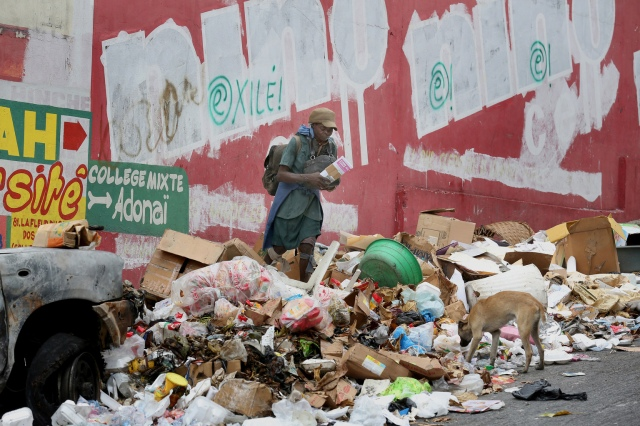 "A woman and dog are seen amid garbage along a street in 2015 in Port-au-Prince, Haiti. Blessed Paul VI's 1967 encyclical ""Populorum Progressio"" rooted the Catholic Church in solidarity with the world's poorest nations. (CNS/Bob Roller)"