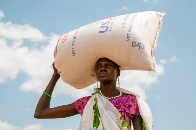 A woman carries food provided by U.S. Agency for International Development in Pajut, South Sudan, March 17. (CNS/Nancy McNally, Catholic Relief Services)