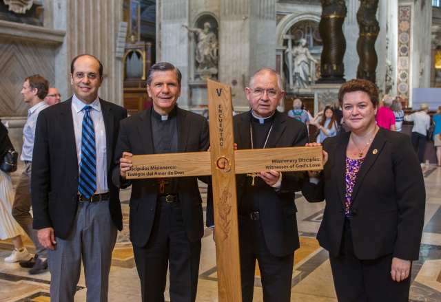 Leaders in ministry to U.S. Hispanic Catholics stand in St. Peter's Basilica at the Vatican in 2016 with the Encuentro cross. They are from left: Alejandro Aguilera-Titus, national coordinator of the Fifth Encuentro; Archbishop Gustavo Garcia-Siller of San Antonio, chairman of the U.S. bishops' Committee on Cultural Diversity in the Church; Archbishop Jose H. Gomez of Los Angeles; and Mar Munoz-Visoso, executive director of the U.S. bishops' Secretariat of Cultural Diversity in the Church. (CNS/Robert Duncan)