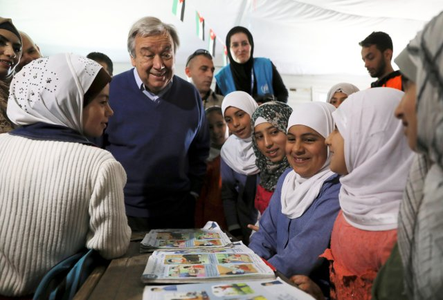 U.N. Secretary-General Antonio Guterres smiles as he visits with Syrian refugee women March 28 at Zaatari camp near Mafraq, Jordan. As the Catholic secretary-general visited the world's biggest camp for Syrian refugees, he made an impassioned plea: Stop Syria's devastating war. (CNS/Reuters)
