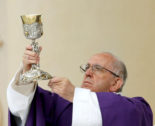 Pope Francis elevates the chalice as he celebrates Mass in Carpi, Italy, April 2. (CNS/Reuters)