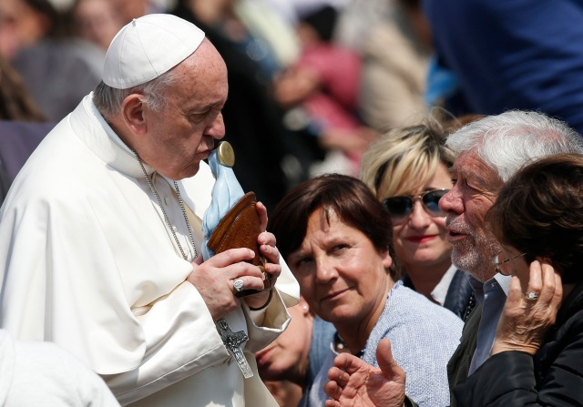 Pope Francis kisses a Marian statue presented by someone in the crowd during his general audience in St. Peter's Square at the Vatican April 5. (CNS/Paul Haring)
