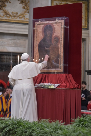 "Pope Francis touches the Marian icon, ""Salus Populi Romani,"" (health of the Roman people), during an evening prayer vigil with young people at the Basilica of St. Mary Major in Rome April 8. (CNS/L'Osservatore Romano)"
