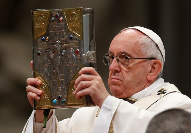 Pope Francis raises the Book of the Gospels as he celebrates Holy Thursday chrism Mass in St. Peter's Basilica at the Vatican April 13. (CNS/Paul Haring)