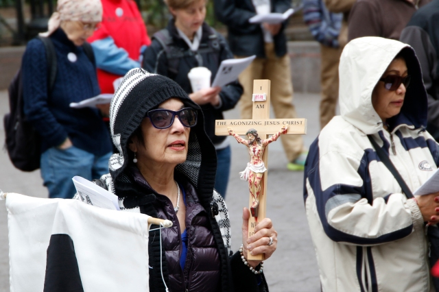 "A woman holds a crucifix during the 35th annual Pax Christi Metro New York Way of the Cross/Way of Peace April 14 in New York City. ""Jesus Calls Us to Active Nonviolence"" was the theme of this year's Good Friday commemoration. (CNS/Gregory A. Shemitz)"