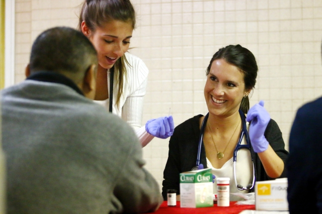 Angelica Italiano and Brighid Imperiale, first-year students at the Philadelphia College of Osteopathic Medicine, screen patients at St. Patrick Parish's church hall in Norristown, Pa. (CNS/Sarah Webb, CatholicPhilly)