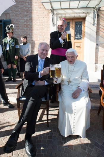 Retired Pope Benedict XVI raises a glass of beer with Bavarian Prime Minister Horst Seehofer during the German pontiff's 90th birthday celebration April 17 at the Vatican. (CNS/L'Osservatore Romano)