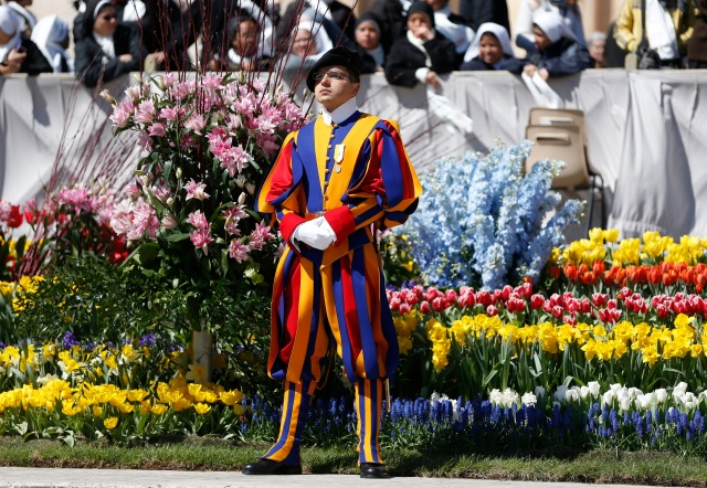 A Swiss Guard stands next to Easter flowers as Pope Francis leads his general audience in St. Peter's Square at the Vatican April 19. (CNS/Paul Haring)