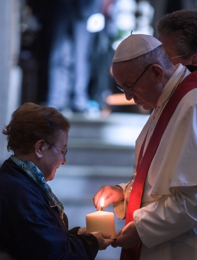 Pope Francis lights a candle during a prayer service at the Basilica of St. Bartholomew in Rome April 22. The service was in memory of Christians killed for their faith in the 20th and 21st centuries. (CNS/Maria Grazia Picciarella, pool)