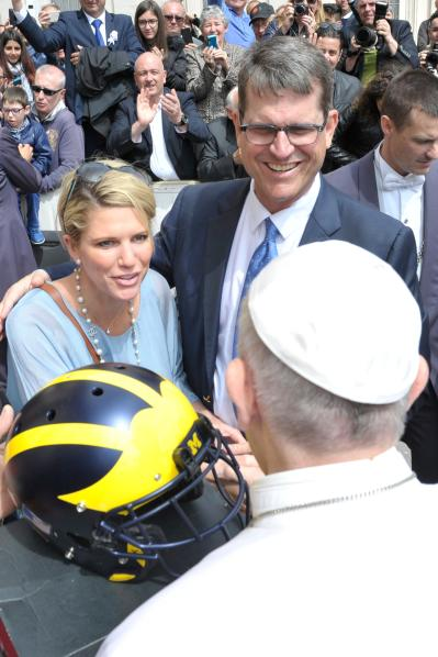 Jim Harbaugh, head football coach for the University of Michigan, and his wife, Sarah, chat with Pope Francis after presenting him with a team football helmet during the pope's general audience April 26. (CNS/L'Osservatore Romano)