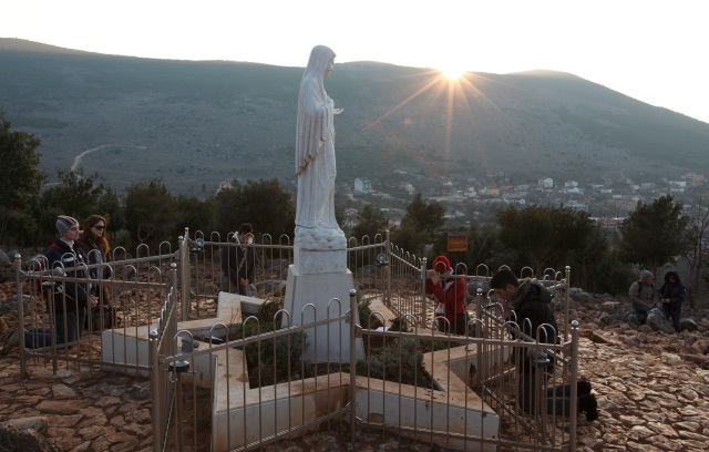 Pilgrims pray around a statue of Mary on Apparition Hill in Medjugorje, Bosnia-Herzegovina, in this 2011 file photo. (CNS/Paul Haring)