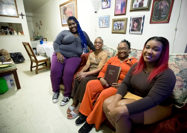 Crystal Morris, holding Bible, poses with her sister Bernadette Johnson and her two daughters, Cierra, far left, and Candace, right. (CNS/Tyler Orsburn)