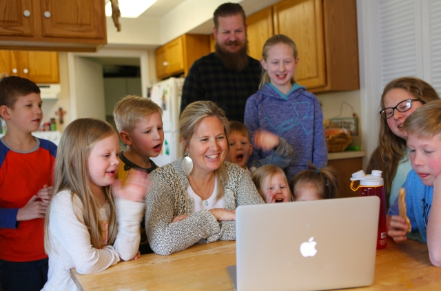 Amy and Ryan Laddbush of Bowie, Md., along with nine of their 11 children, enjoy a FaceTime call with their oldest son, who is attending college at Salisbury University in Salisbury, Md. (CNS/Chaz Muth)