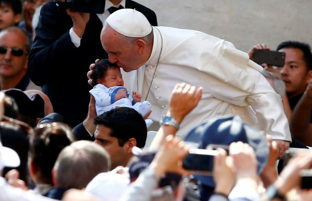 Pope Francis kisses a baby as he arrives to lead his general audience in St. Peter's Square May 10. (CNS/Reuters)